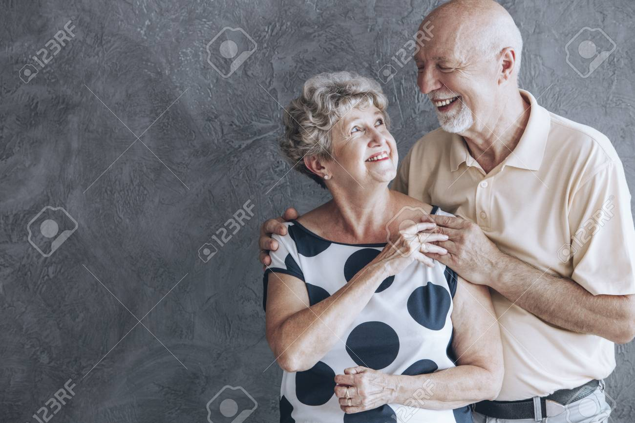Couple of seniors celebrating their wedding anniversary and looking into each other's eyes lovingly - 96096358