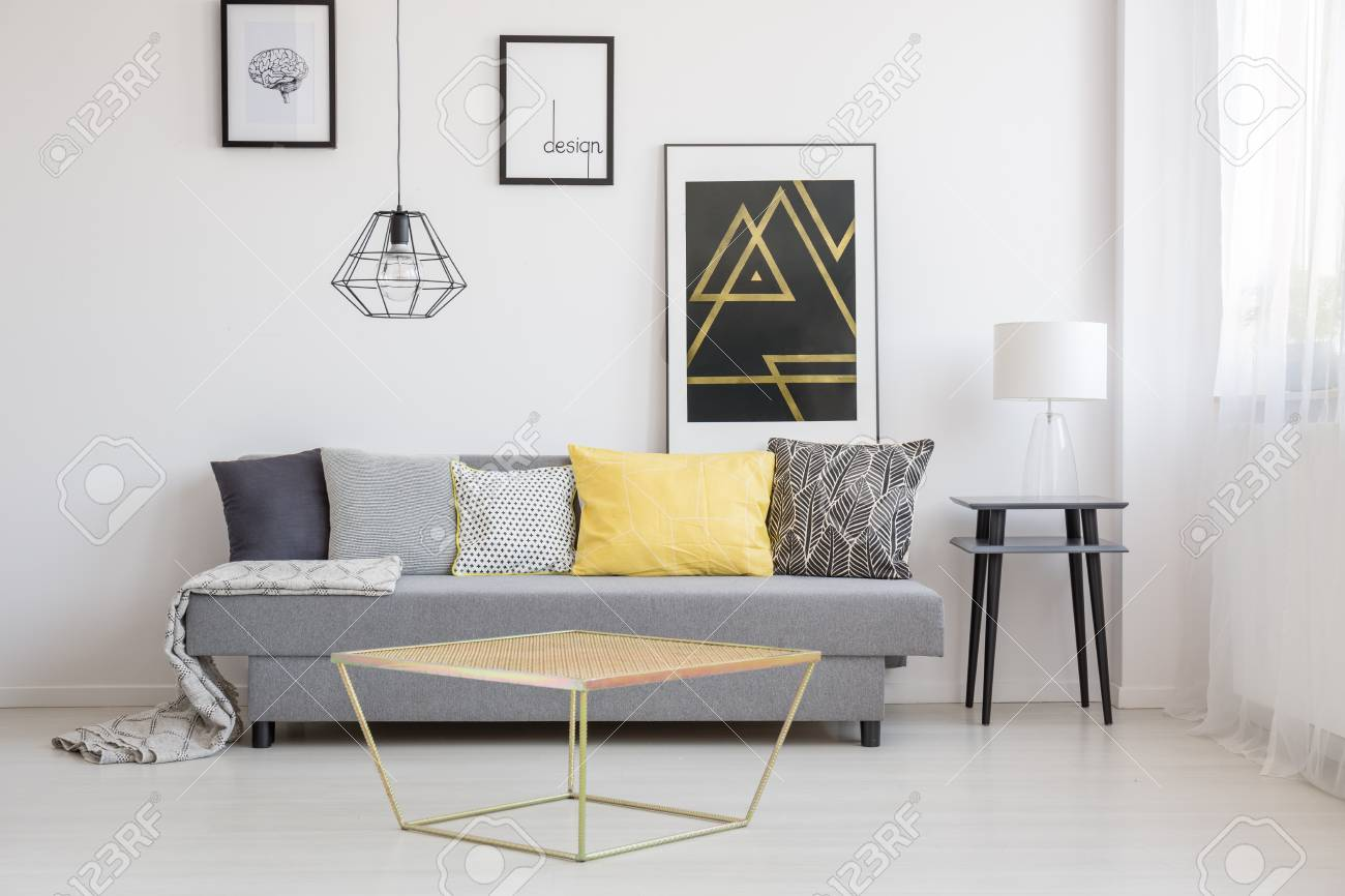 Gold table in front of a gray couch with black, white and yellow..