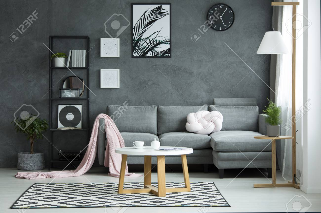Pink Blanket On Sofa And Round Table On Patterned Rug In Grey