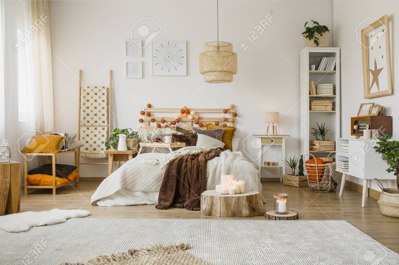 Brown blanket on bed in spacious hygge bedroom interior with..