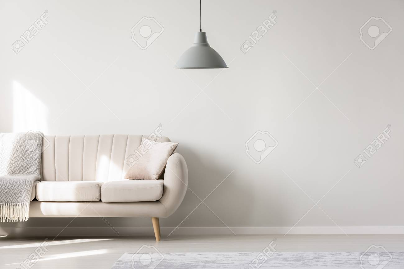 Beige sofa against white, empty wall with copy space in simple living room interior with lamp - 96627774