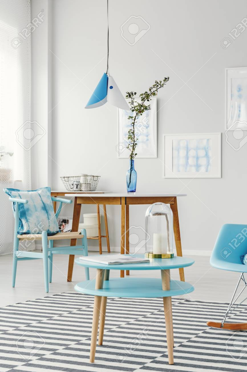 Blue Round Table Next To Wooden Chair In Bright Dining Room Interior With Branch Vase