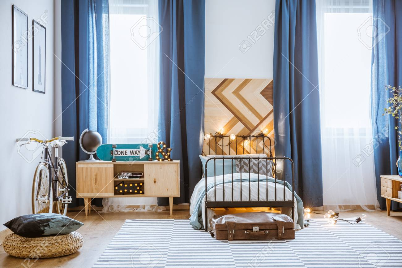 Pouf and bike in cozy teenager\'s bedroom interior with blue curtains..