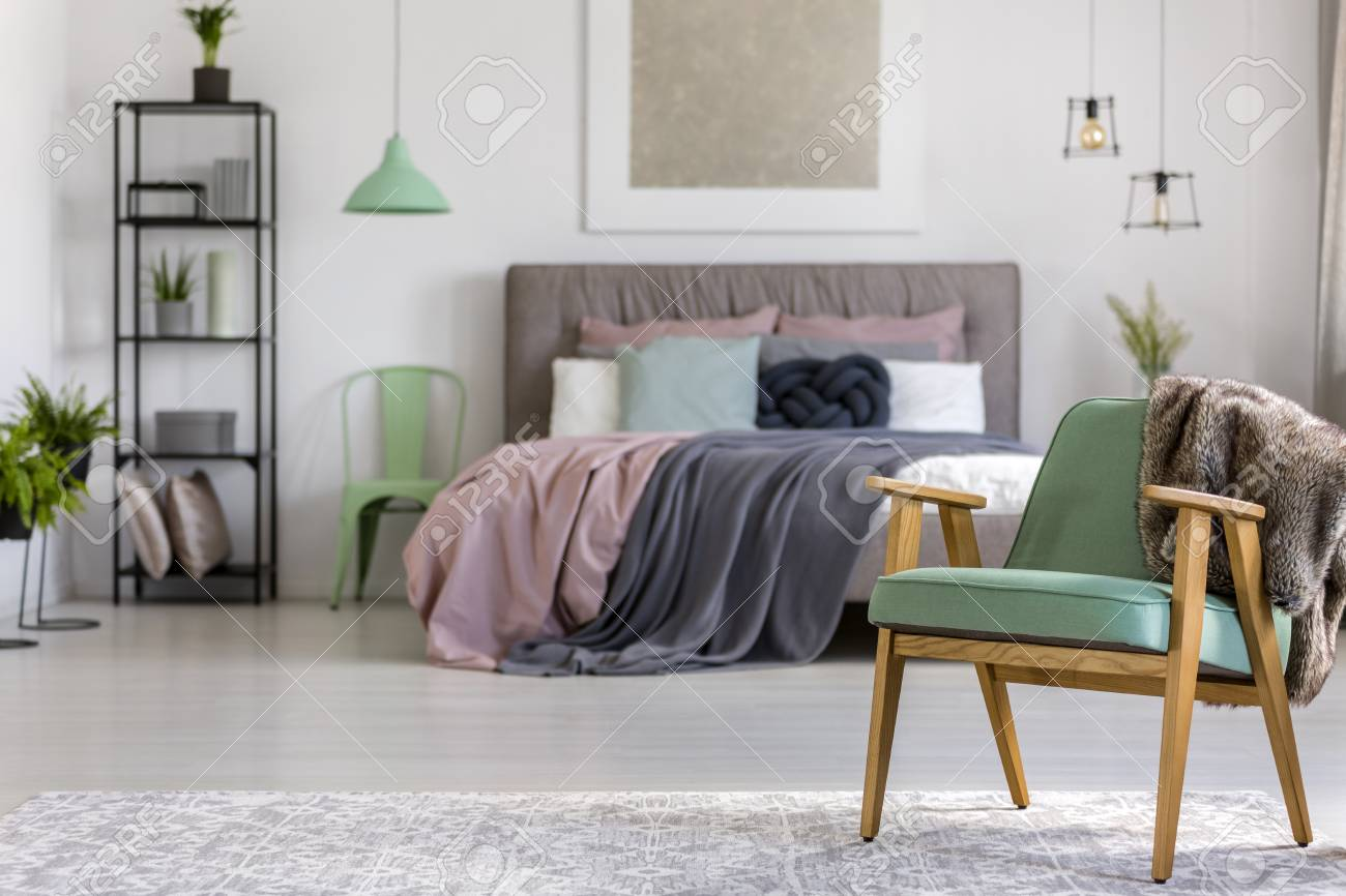 photo green wooden armchair on grey carpet in bedroom interior with lamps and painting above bed