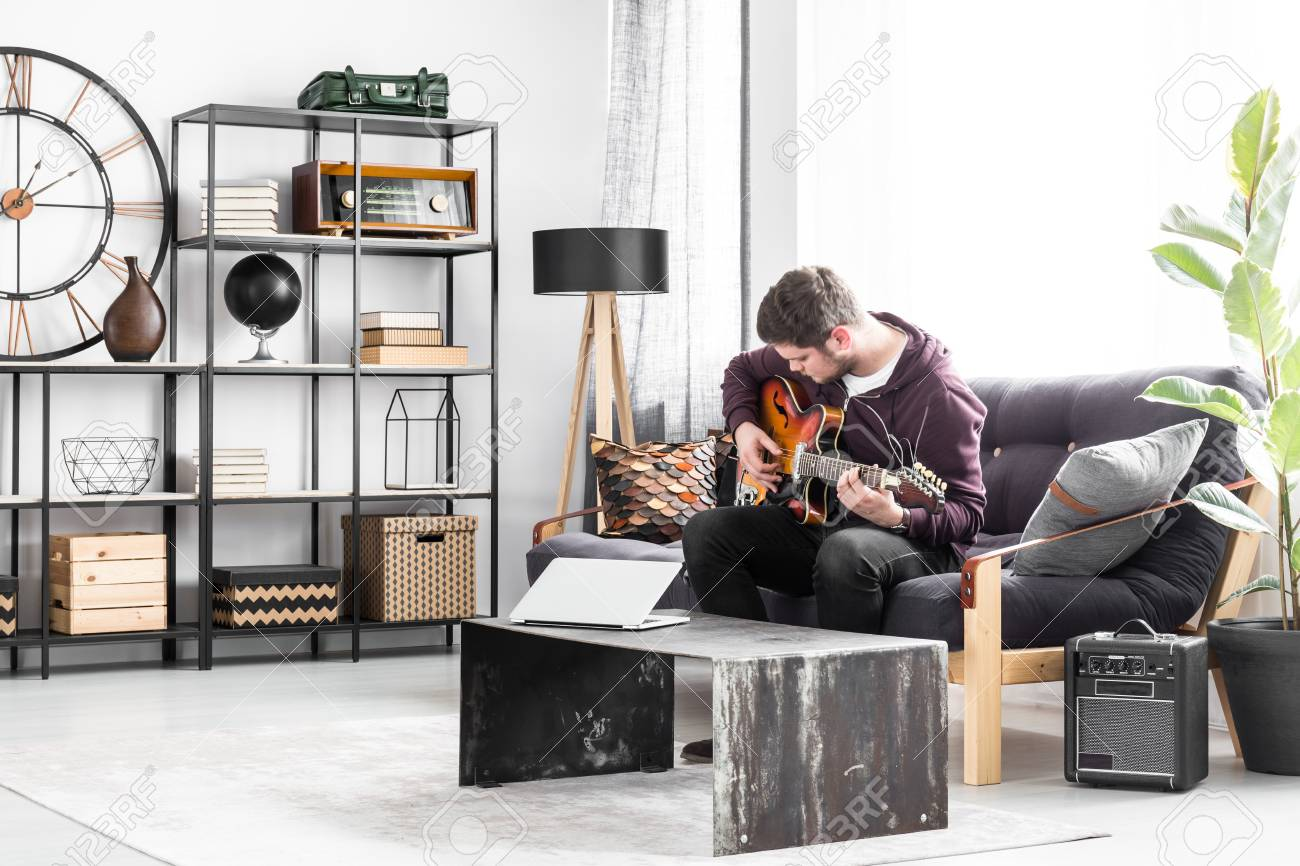 Musician sitting on a black couch and playing the guitar in modern..