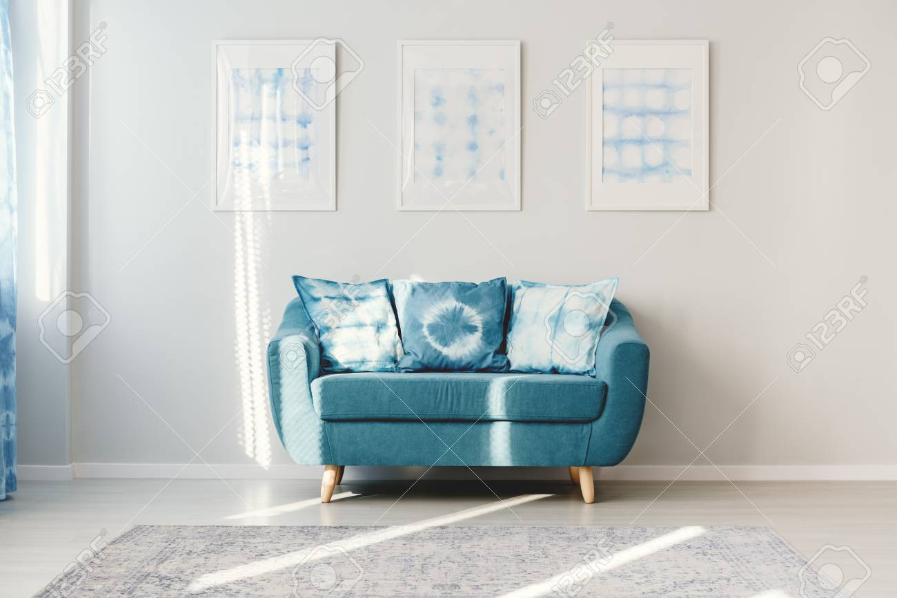 Patterned Cushions On Turquoise Settee Against White Wall With ...