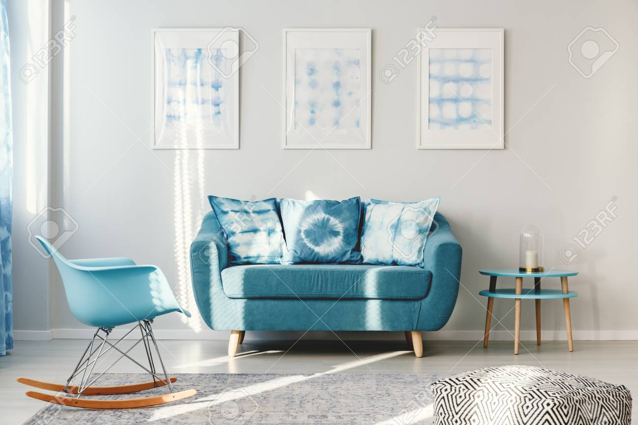turquoise sofa with pillows between round table and blue rocking
