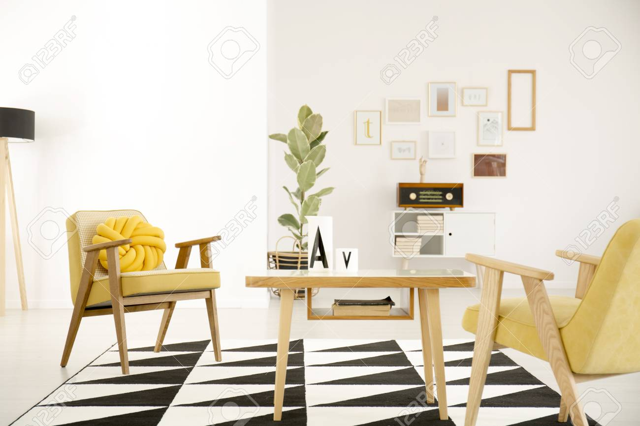 Wooden table and yellow armchairs on black and white carpet in..