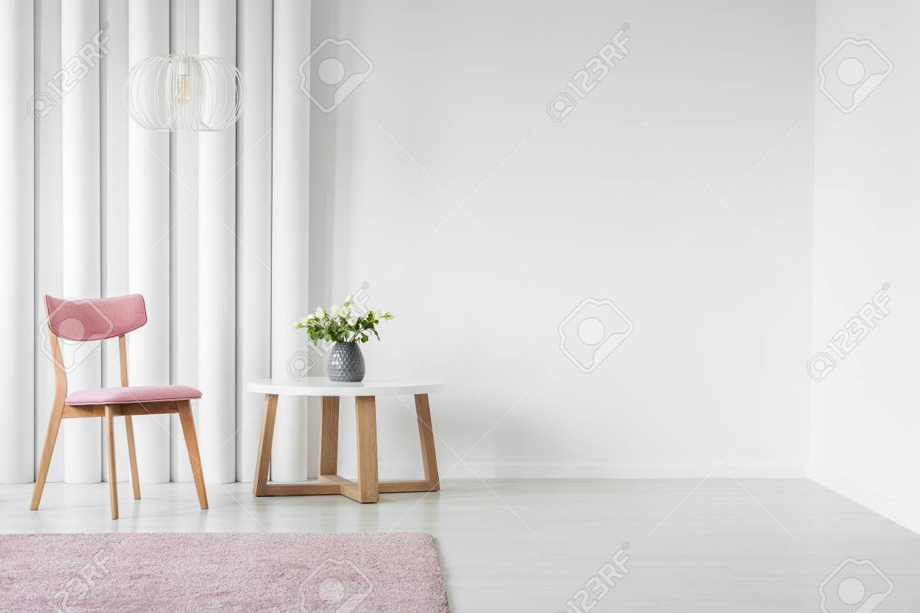 Pink, wooden chair and coffee table next to an empty wall in a living room interior - 96924621