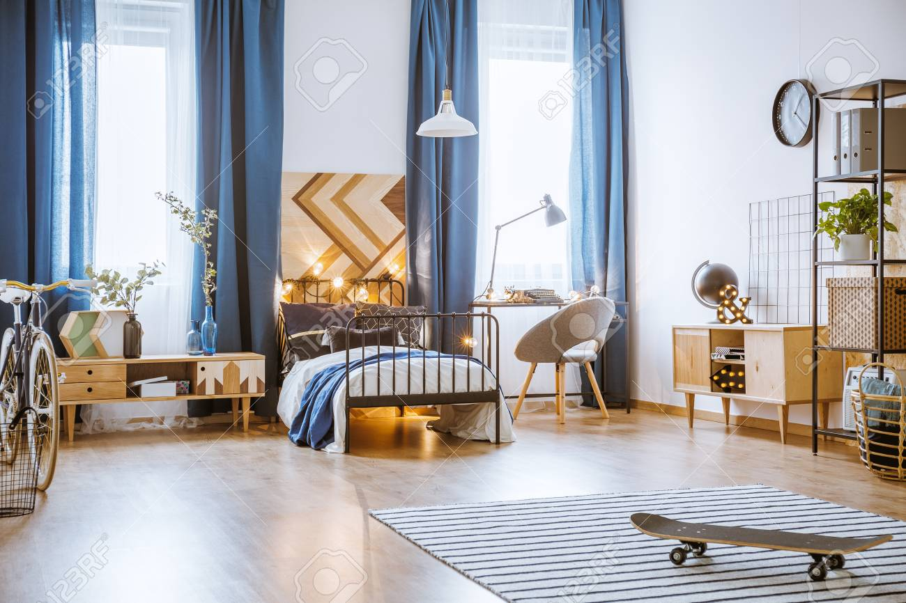 Skateboard On Rug In Spacious Bedroom Interior With Wooden Furniture