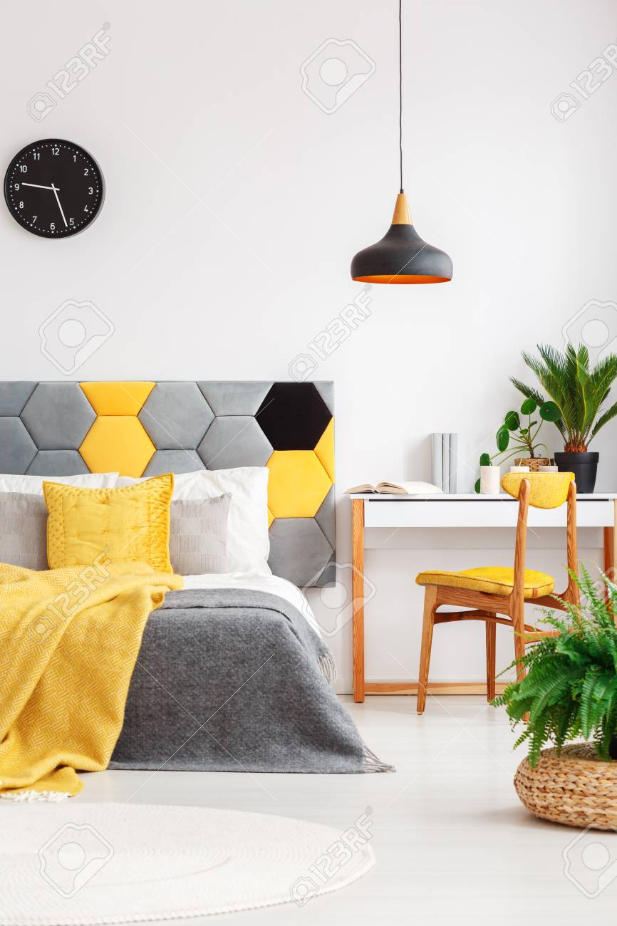Plants in colorful bedroom interior with yellow blanket on gray..