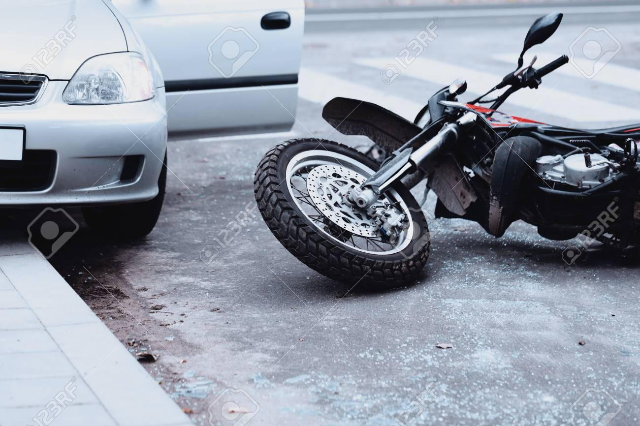 Motorcycle lying on the road and car standing with open door after a collision - 97415360