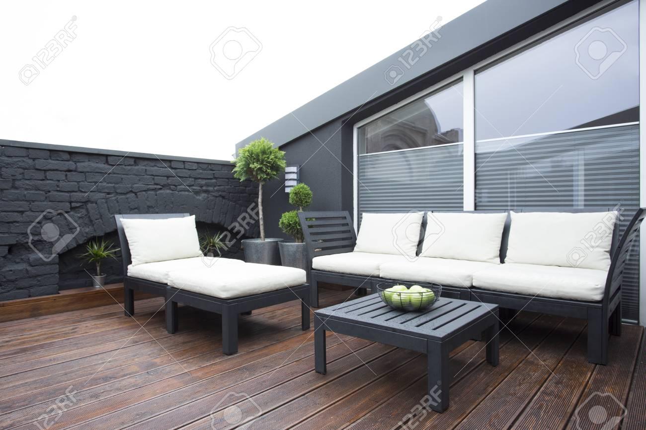 Mobilier de jardin blanc sur la terrasse avec des plantes et plancher en  bois foncé