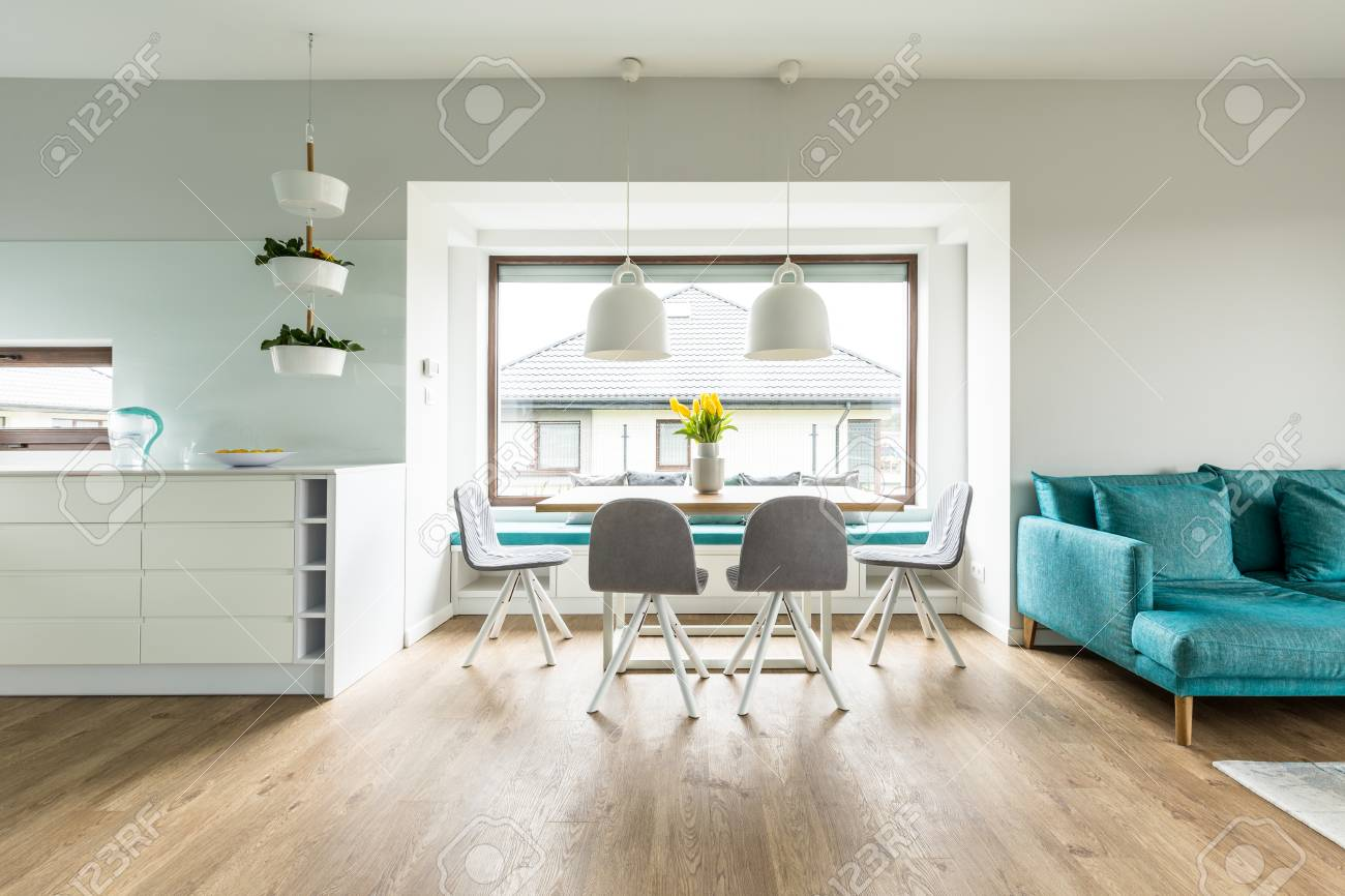 Grey Chairs At Dining Table On Wooden Floor In White Apartment
