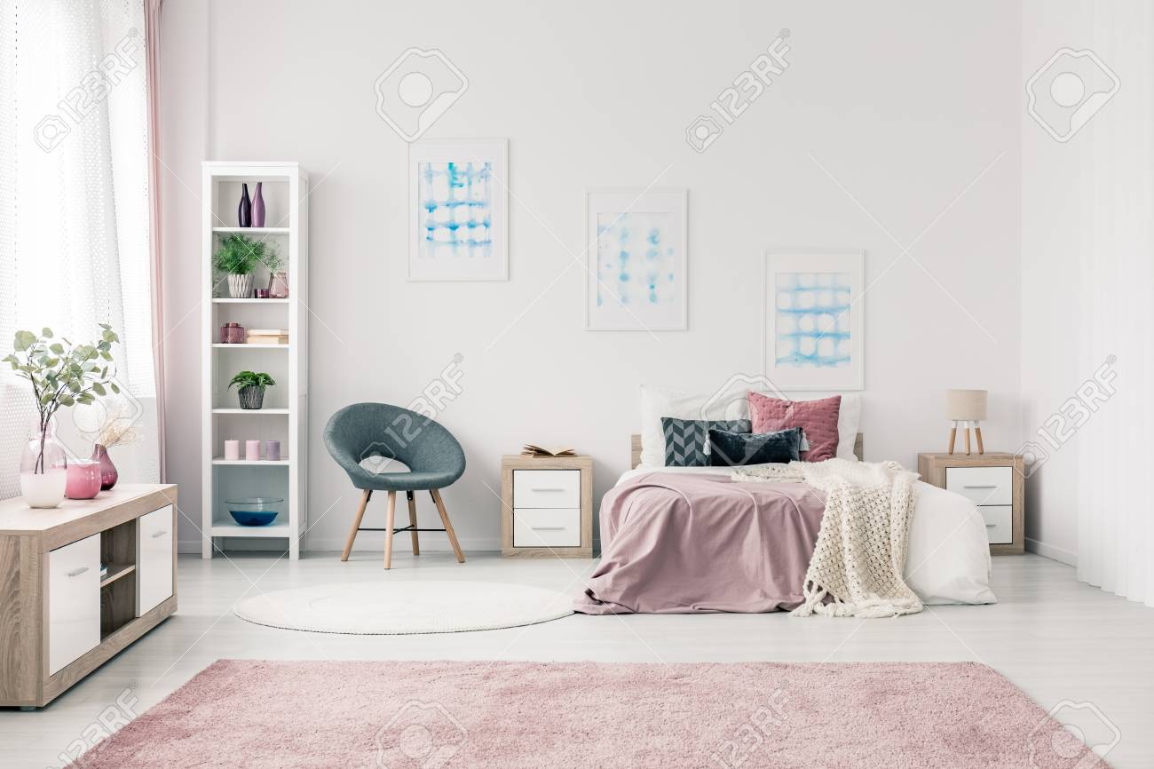 Grey Armchair Next To Bed With Pink Bedsheets In Pastel Bedroom Interior  With Blue Posters Stock