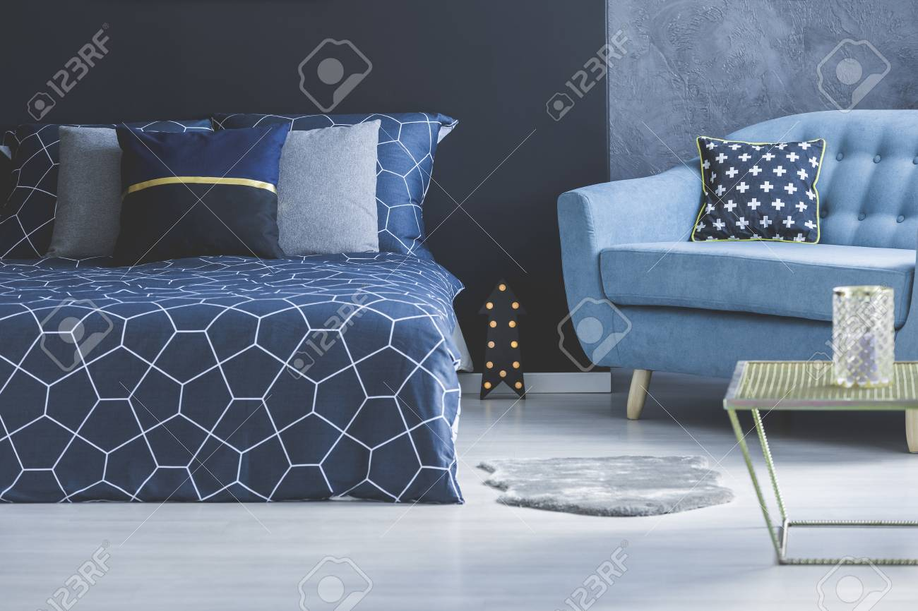 Blue Sofa With Patterned Cushion And Grey Fur Next To A Dark