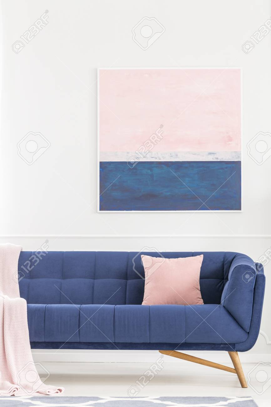Pink pillow on navy blue sofa against white wall with painting..