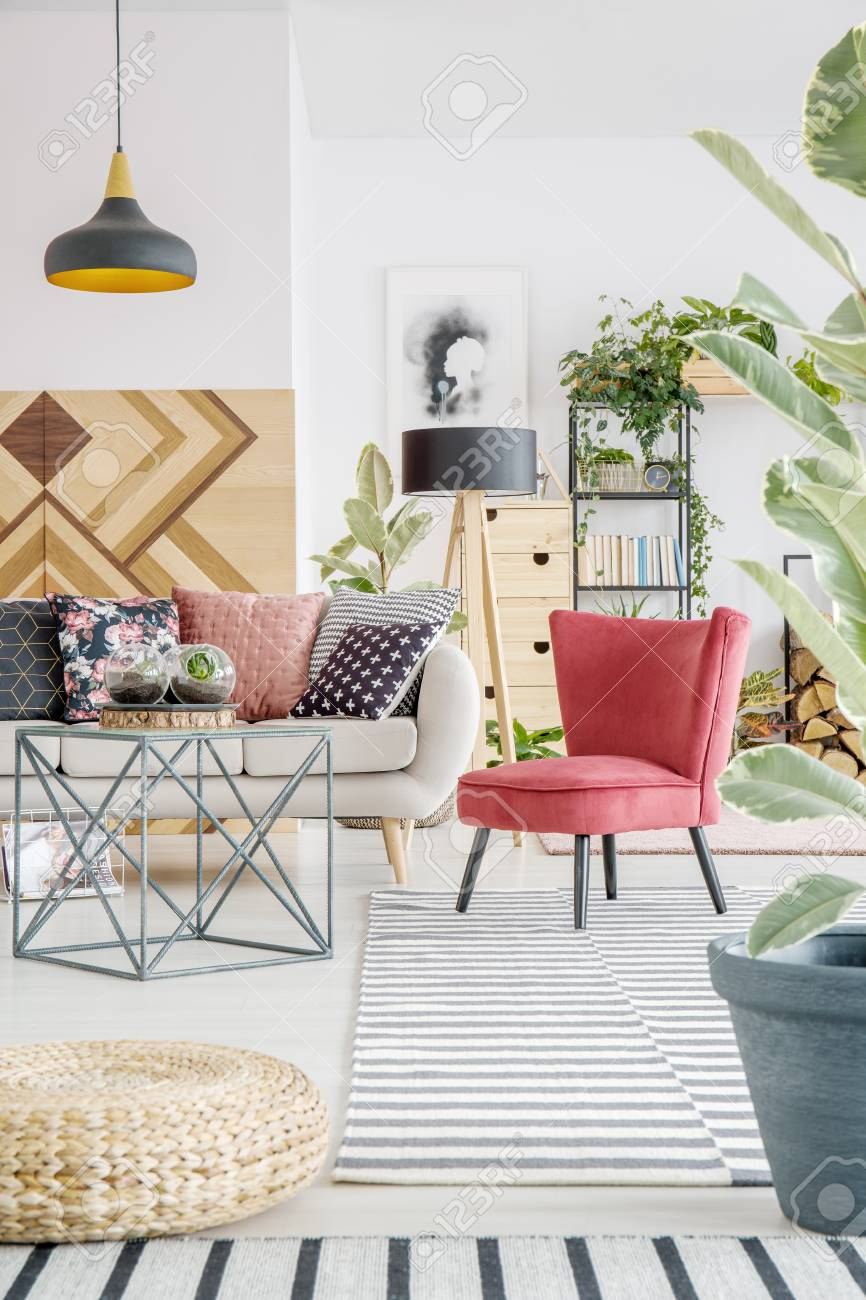 Red Chair On Striped Carpet Next To Table And Beige Settee In ...