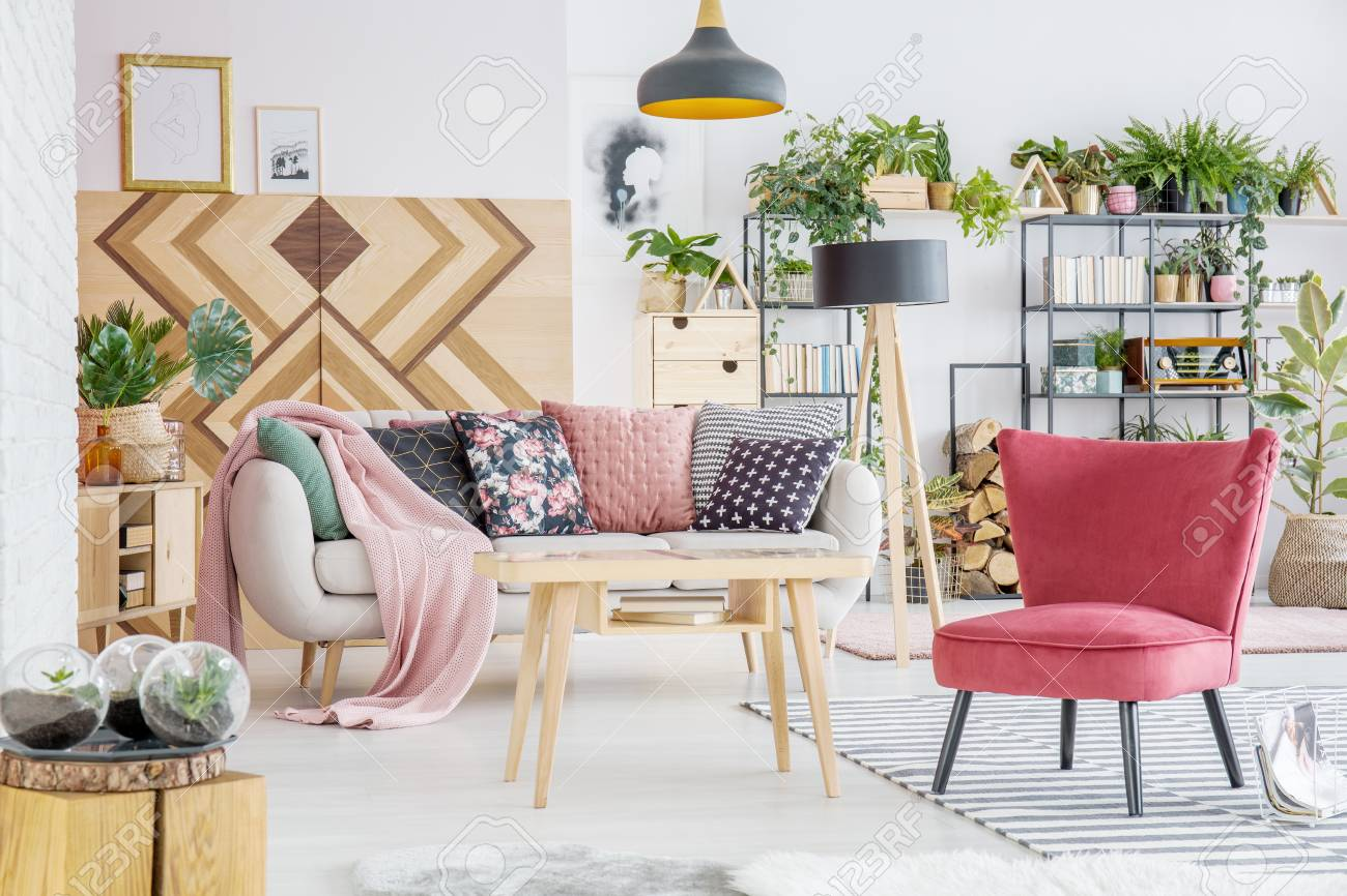 Pink Blanket And Patterned Cushions On Sofa Near Red Chair And ...