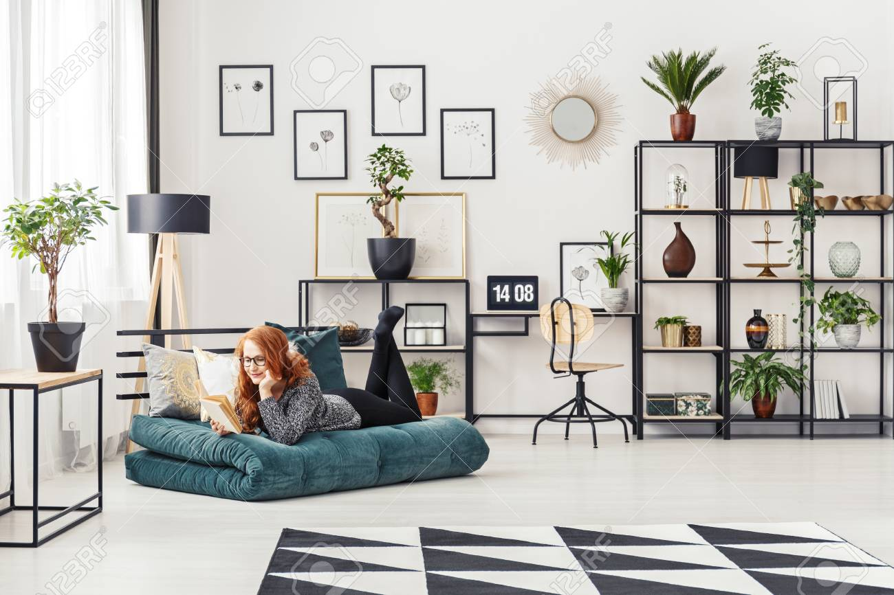 Ginger woman reading a book while lying on a mattress in a modern living room interior & Ginger Woman Reading A Book While Lying On A Mattress In A Modern ...