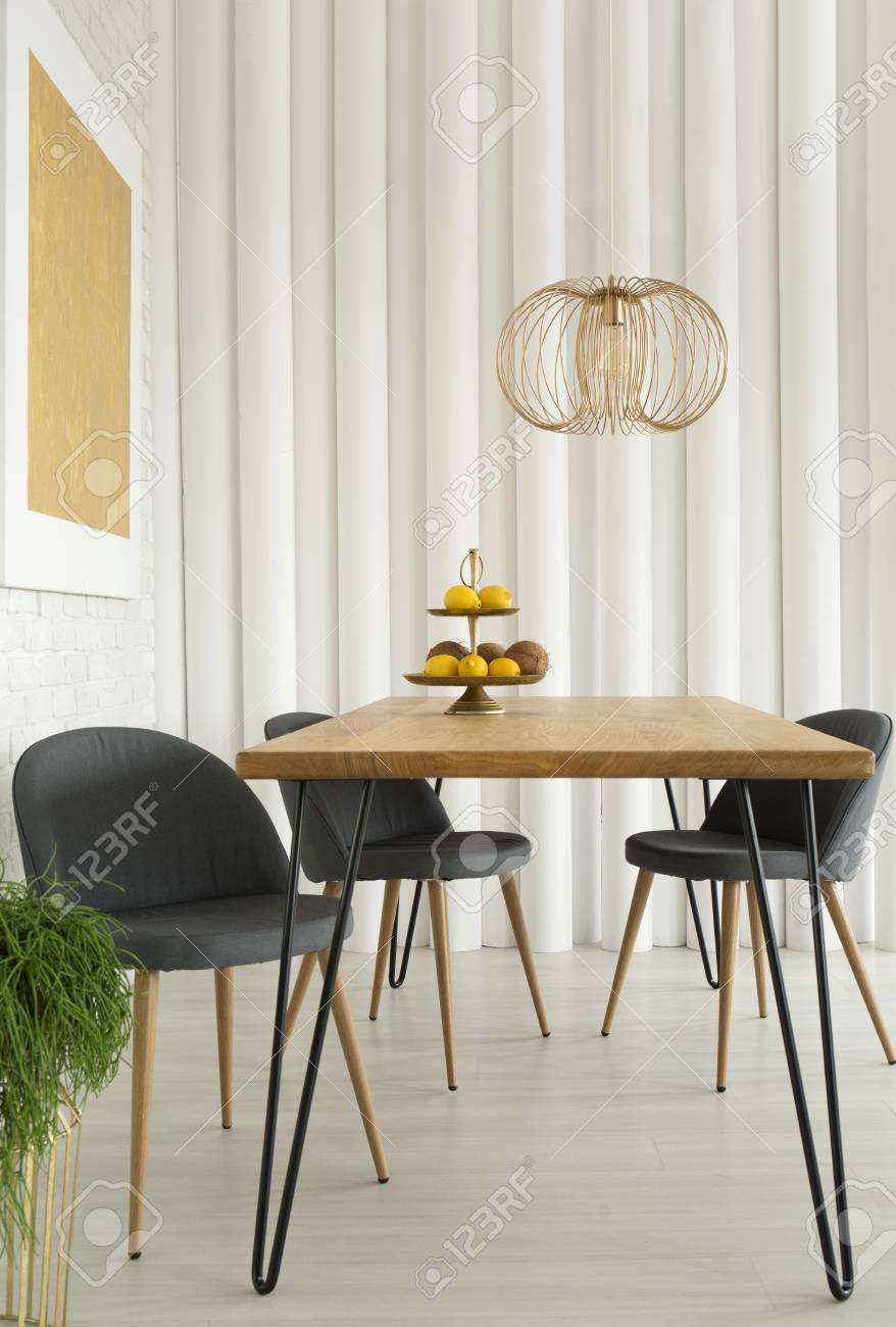 Grey chairs at wooden table under gold lamp in modern dining room interior with painting stock