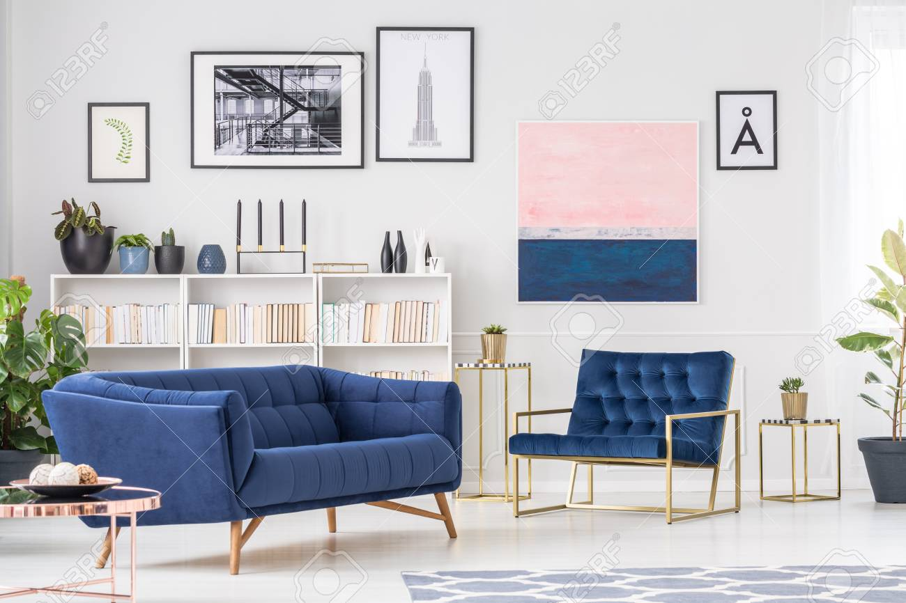 Navy blue sofa in sophisticated living room interior with armchair..