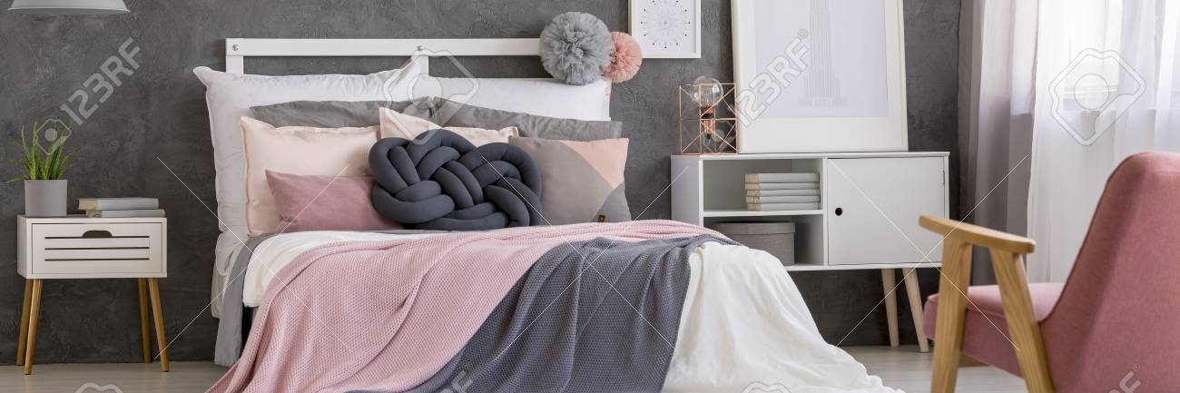 Pastel Pink Bedsheets On Bed With Knot Pillow In Bedroom Interior With  White Nightstand And Cupboard