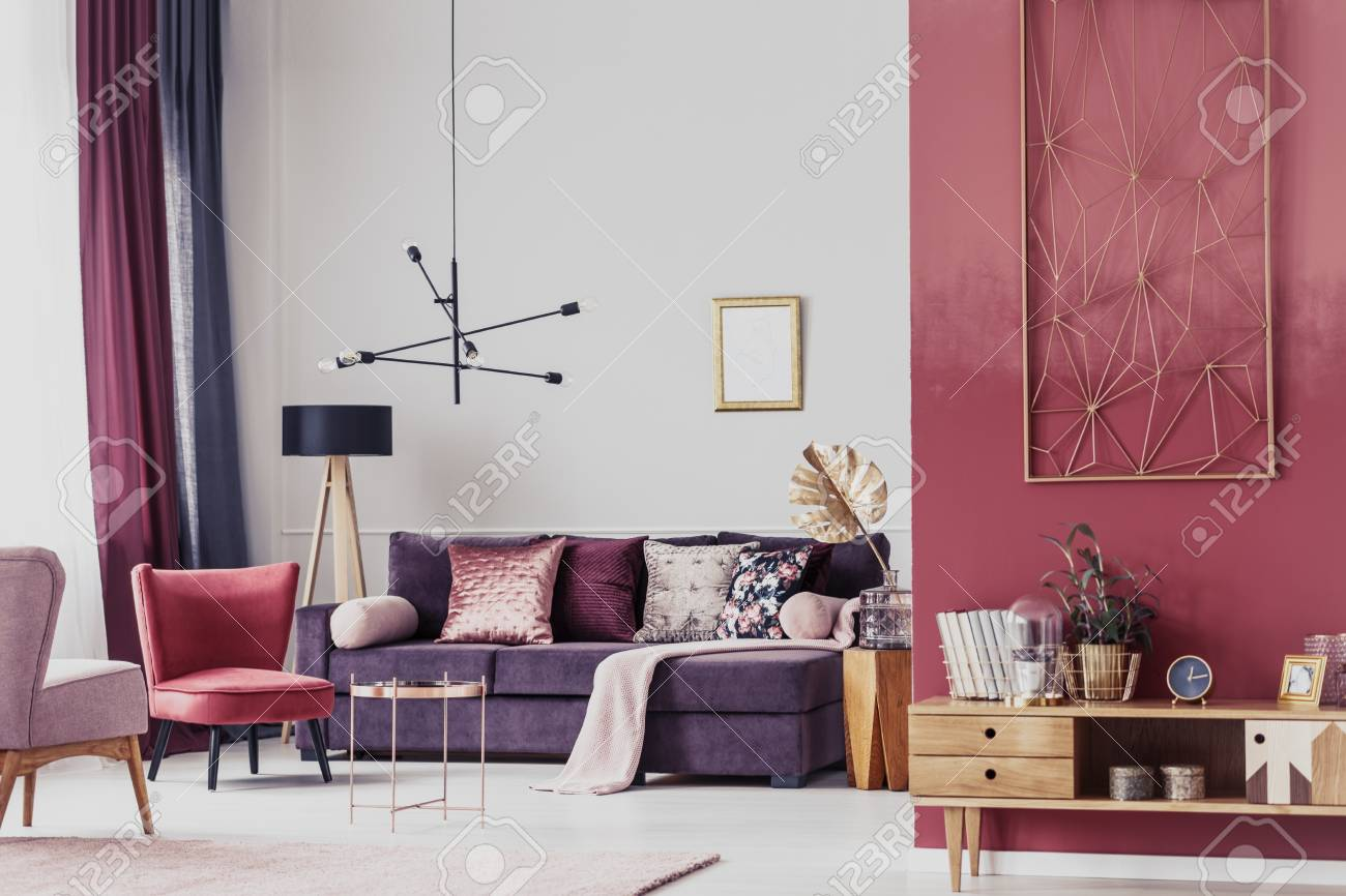 Red Armchair Next To A Purple Settee In Cozy Living Room Interior ...