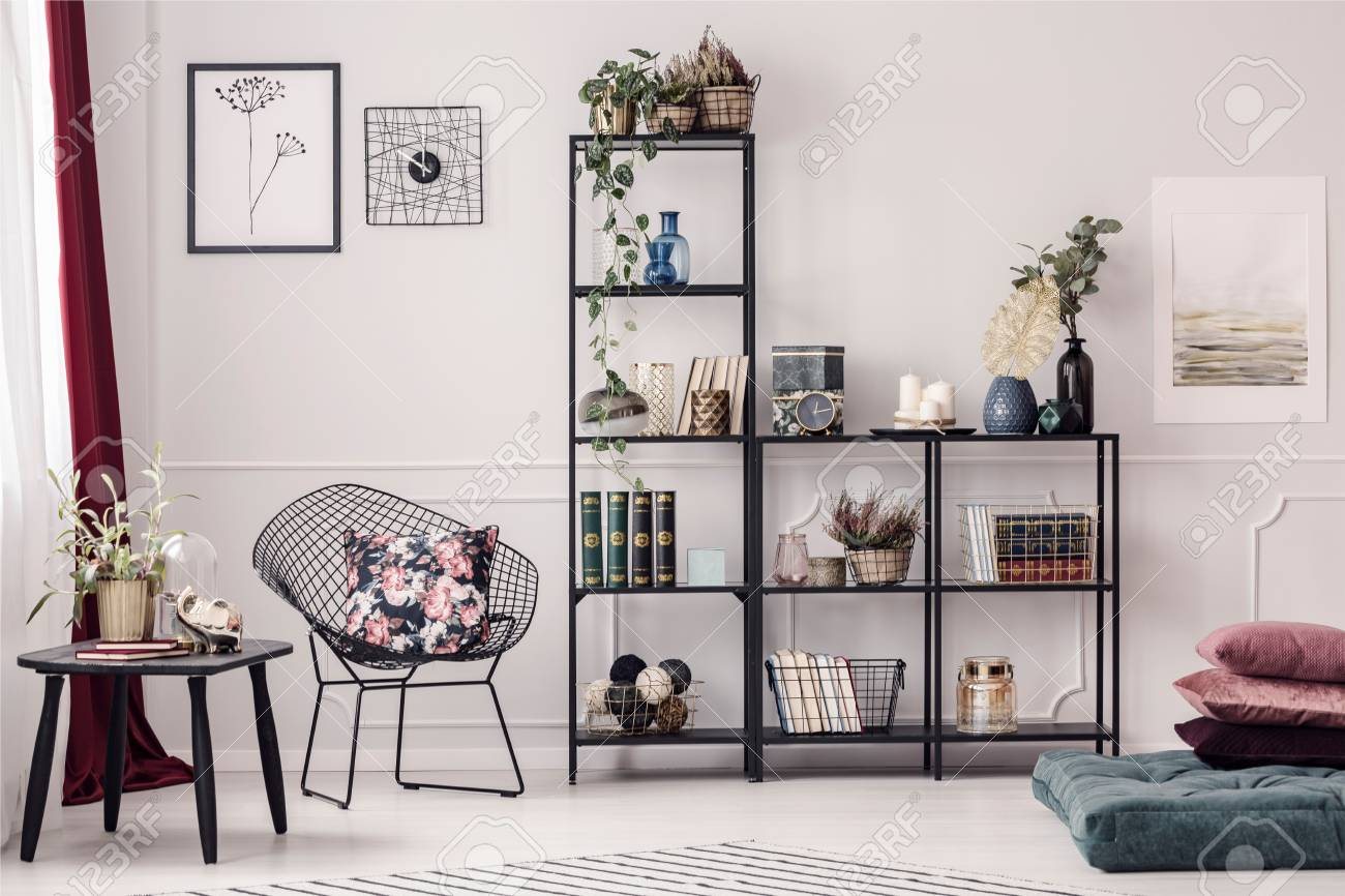 Floral Pillow Placed On A Metal Chair Standing Next To A Black ...