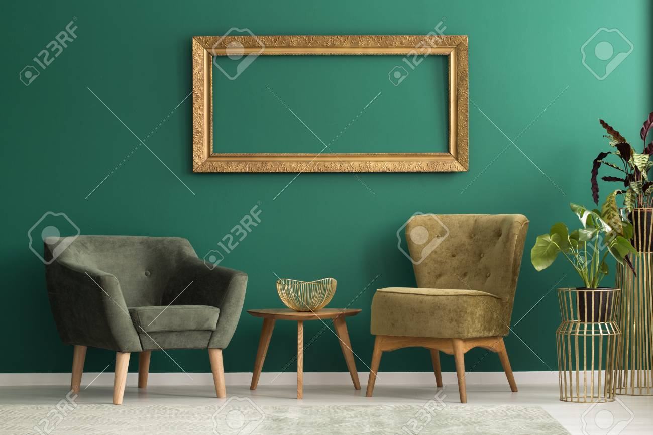 Empty frame above retro upholstered chairs in a green living room interior with plants and