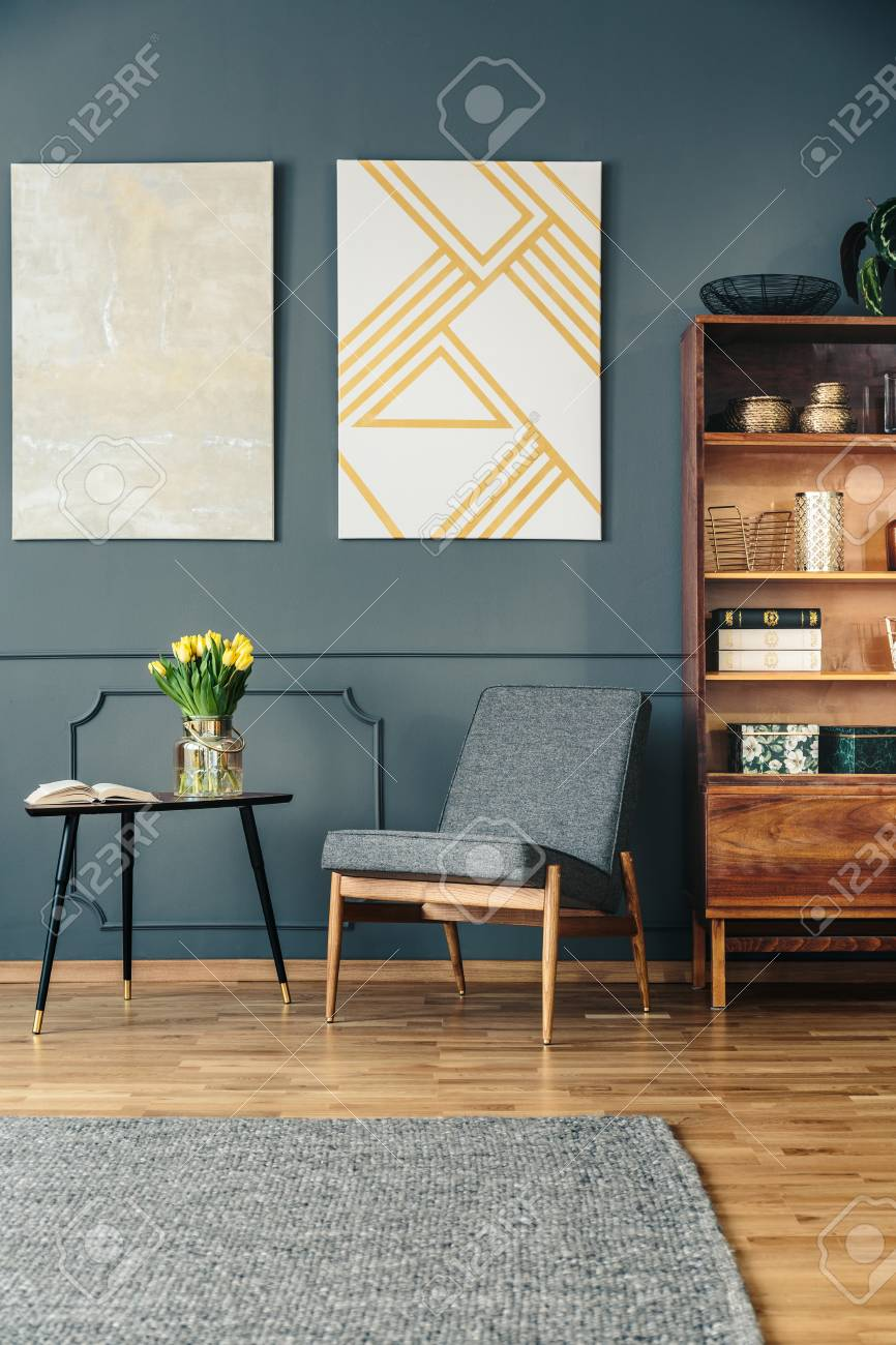 Gray, upholstered chair next to an elegant, wooden bookcase in..