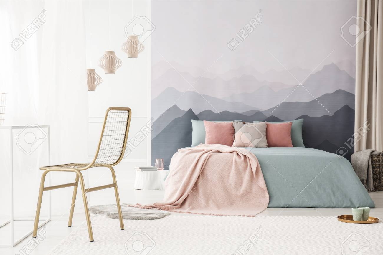 Gold, metal chair in a soft, bright bedroom interior with a mountains..