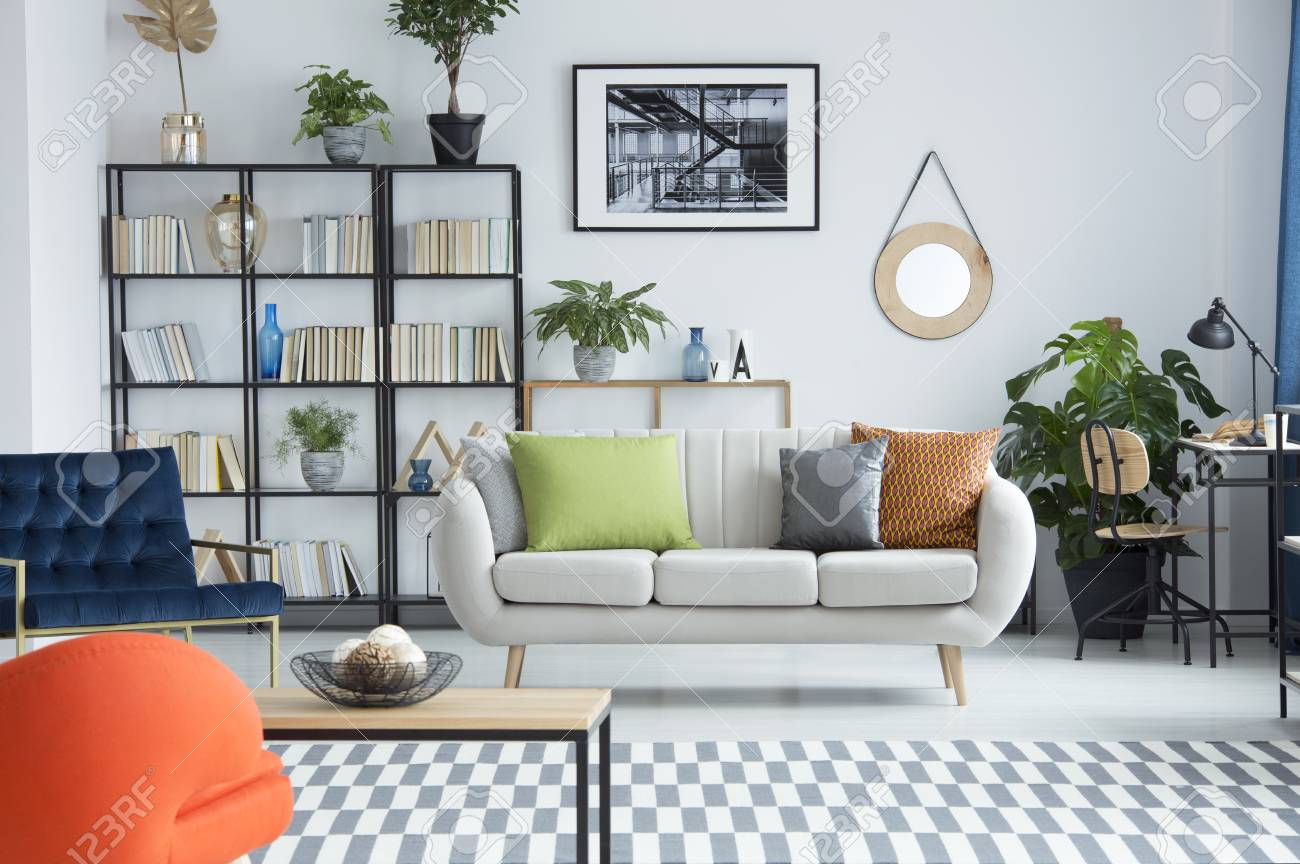 Bright living room interior with books and a sofa standing in..