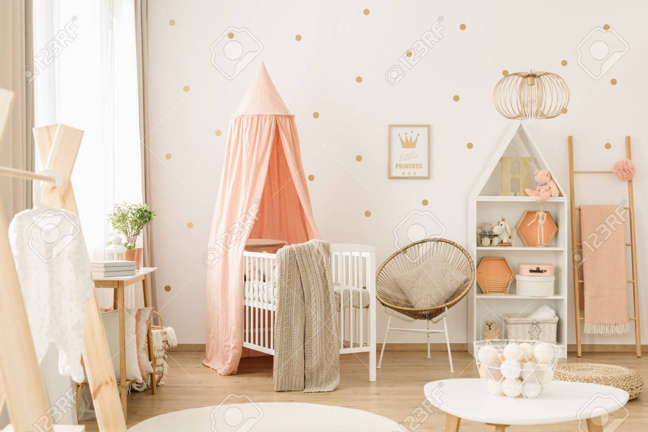 Sweet, spacious nursery room interior for a baby girl with white..