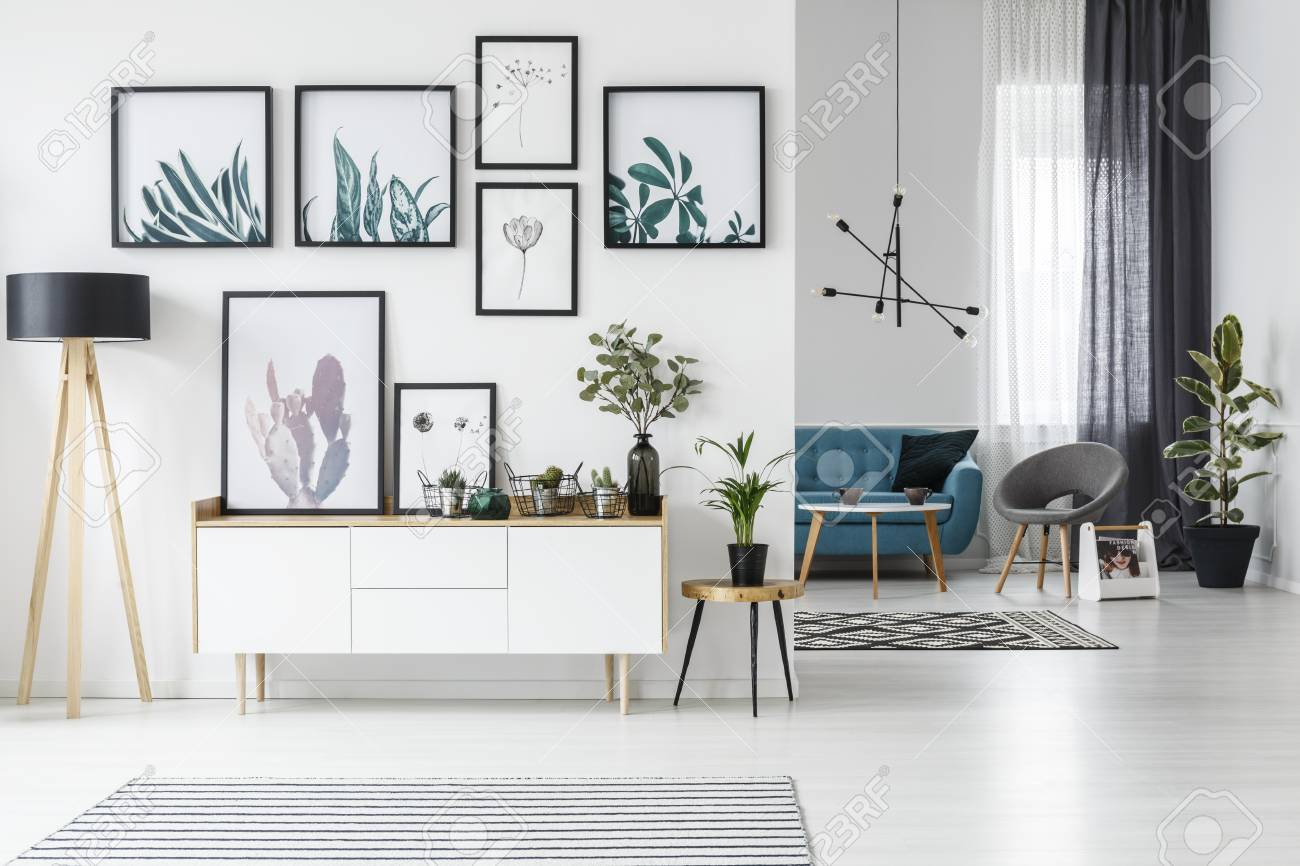 White living room interior with botanical posters on the wall and sofa in the background - 97947696