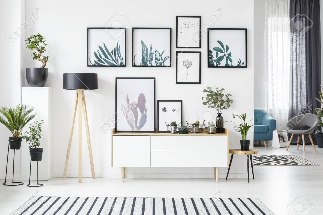 photo botanical posters on the wall in a living room interior with white cabinet wooden lamp and plants