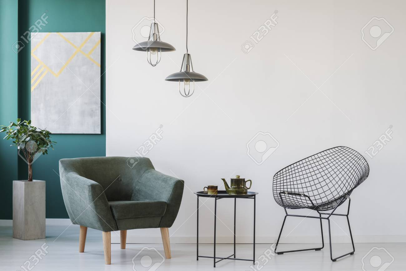 Metal coffee table between armchairs against an empty wall in..