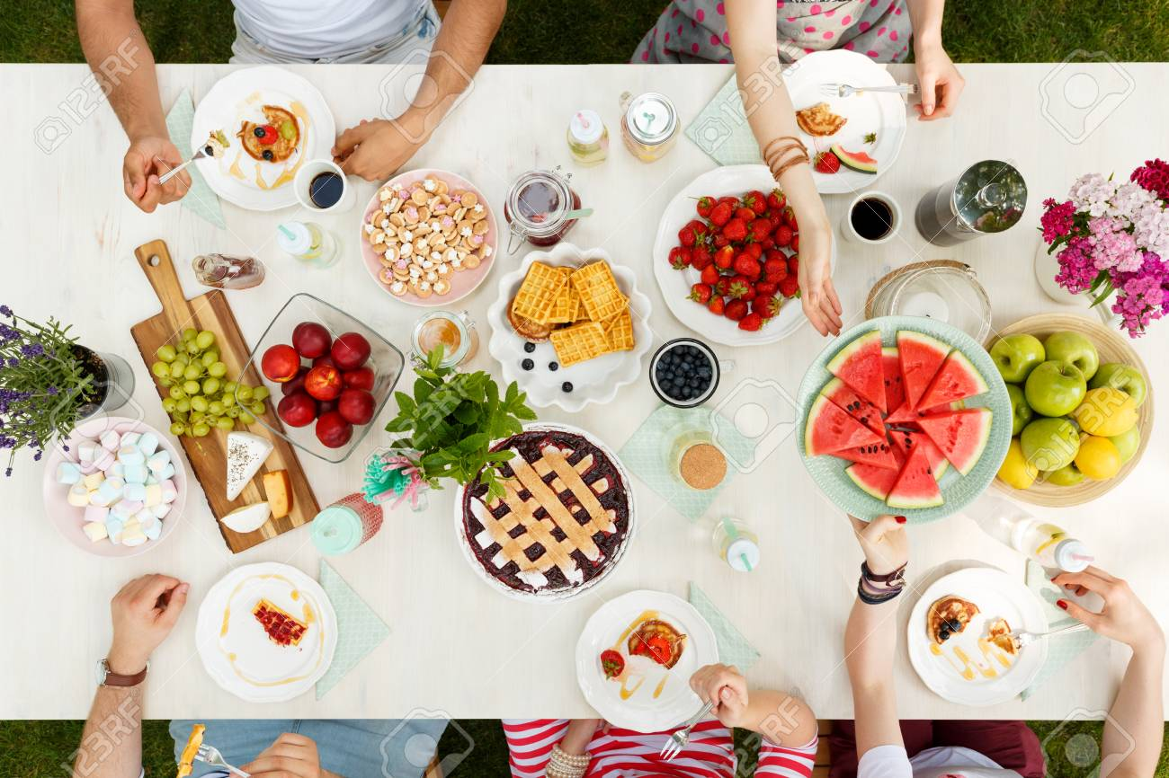 High Angle Of People Sharing A Watermelon At A Table With Fruits