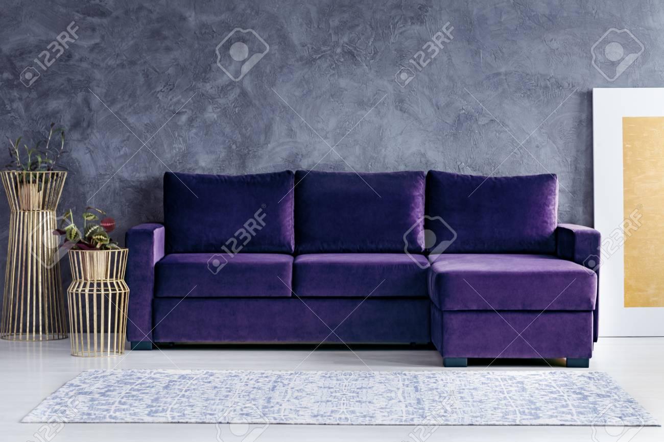 Velvet Corner Sofa Next To Gold Pots In Glamour Living Room Interior