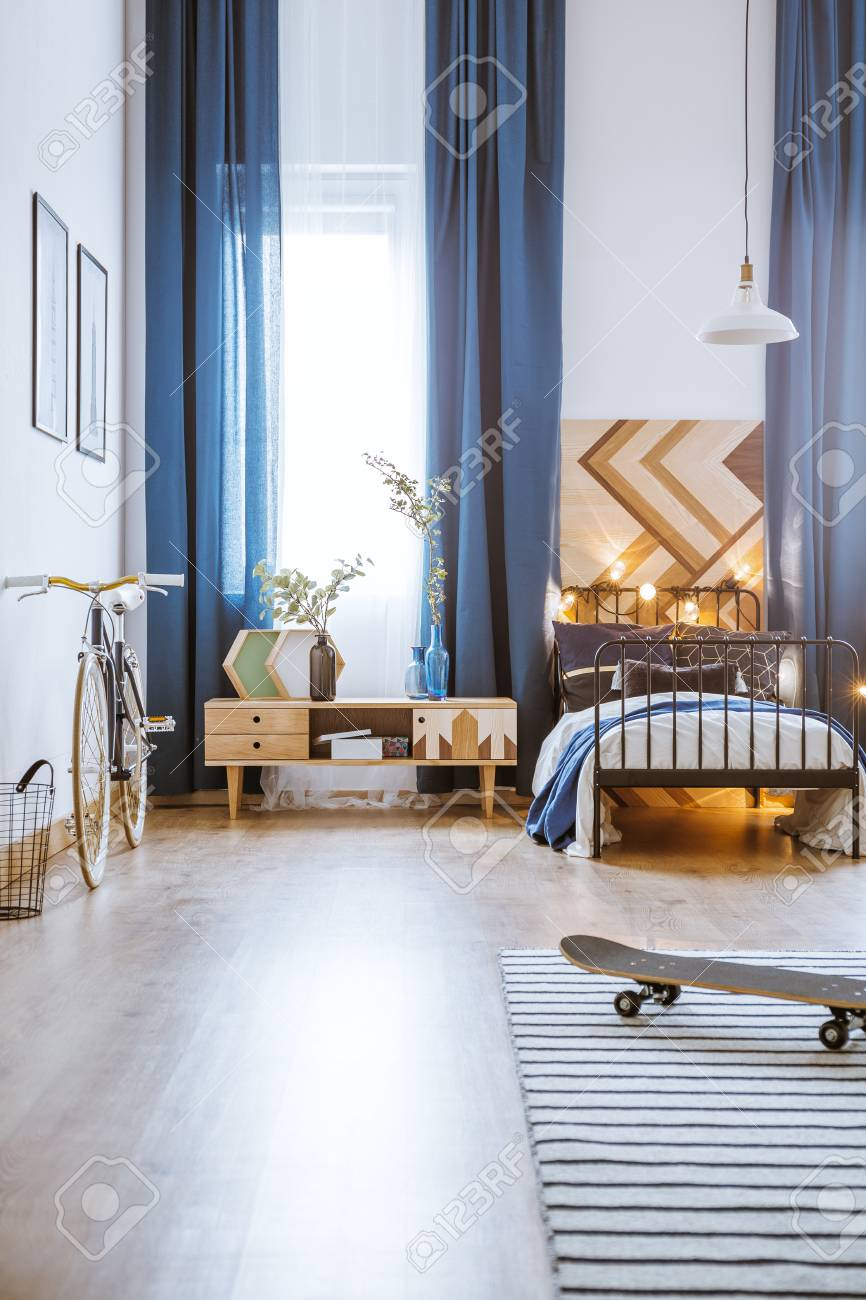 Modern bedroom interior for a teenager with long curtains, bed,..