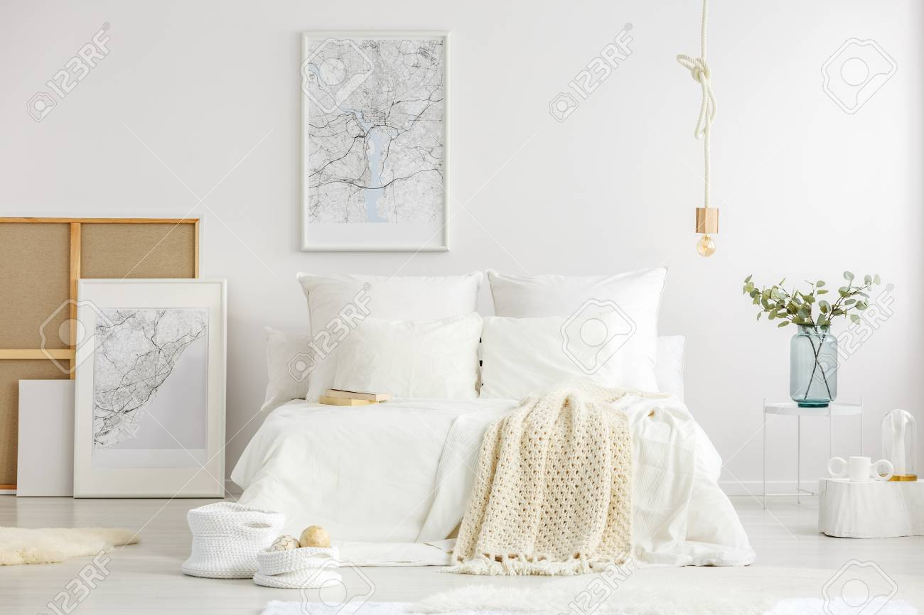 World cities map posters in a white minimalist master bedroom..