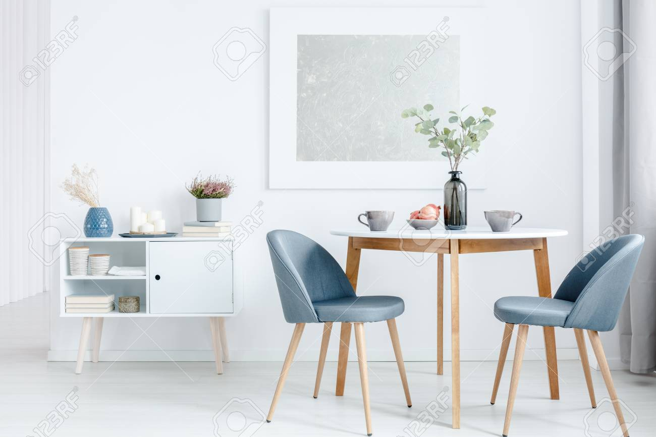 Small dining table with two upholstered chairs and a white cabinet in a bright open