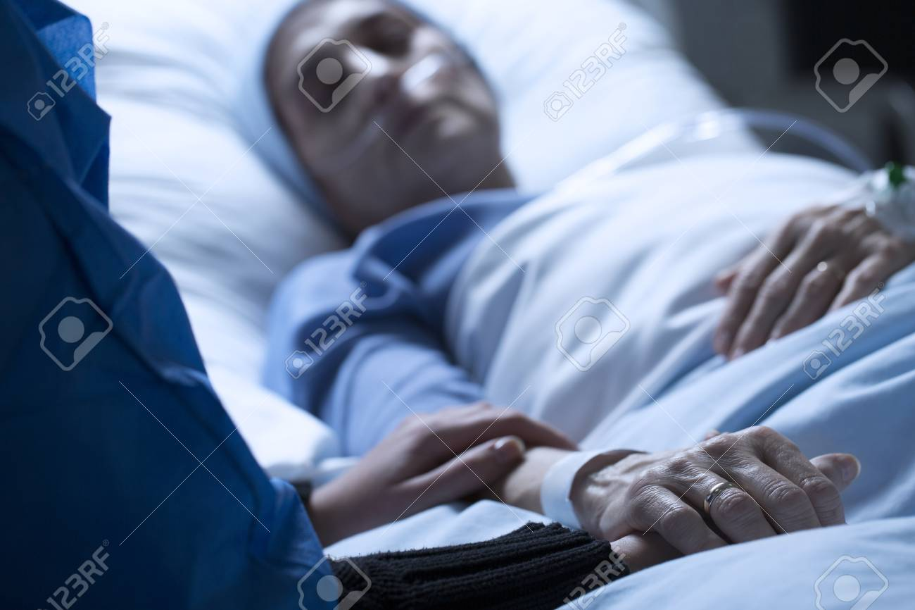Young woman saying goodbye to her mother dying of cancer in a hospice, holding her hand - 98832680