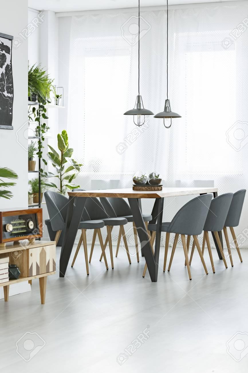 Lampade Sopra Tavolo Da Pranzo lampade sopra il tavolo e le sedie di legno nell'interno luminoso della  sala da pranzo con la retro radio sull'armadio