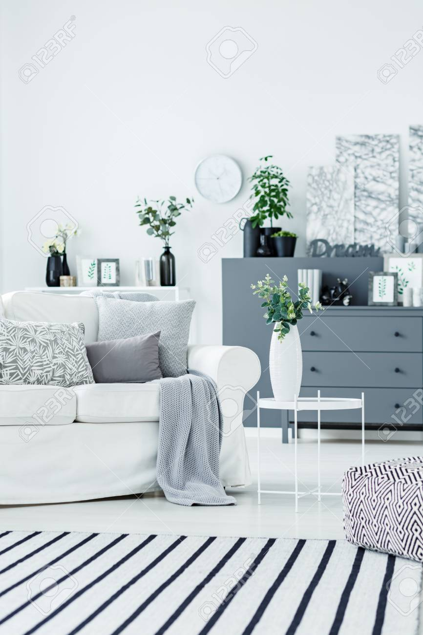 Elegant white vase with plant leaves on a side table in a classy living room interior