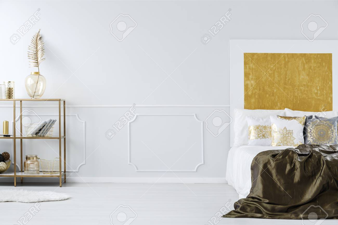 King Size Bed Empty Wall And Golden Shelf With Decorations In