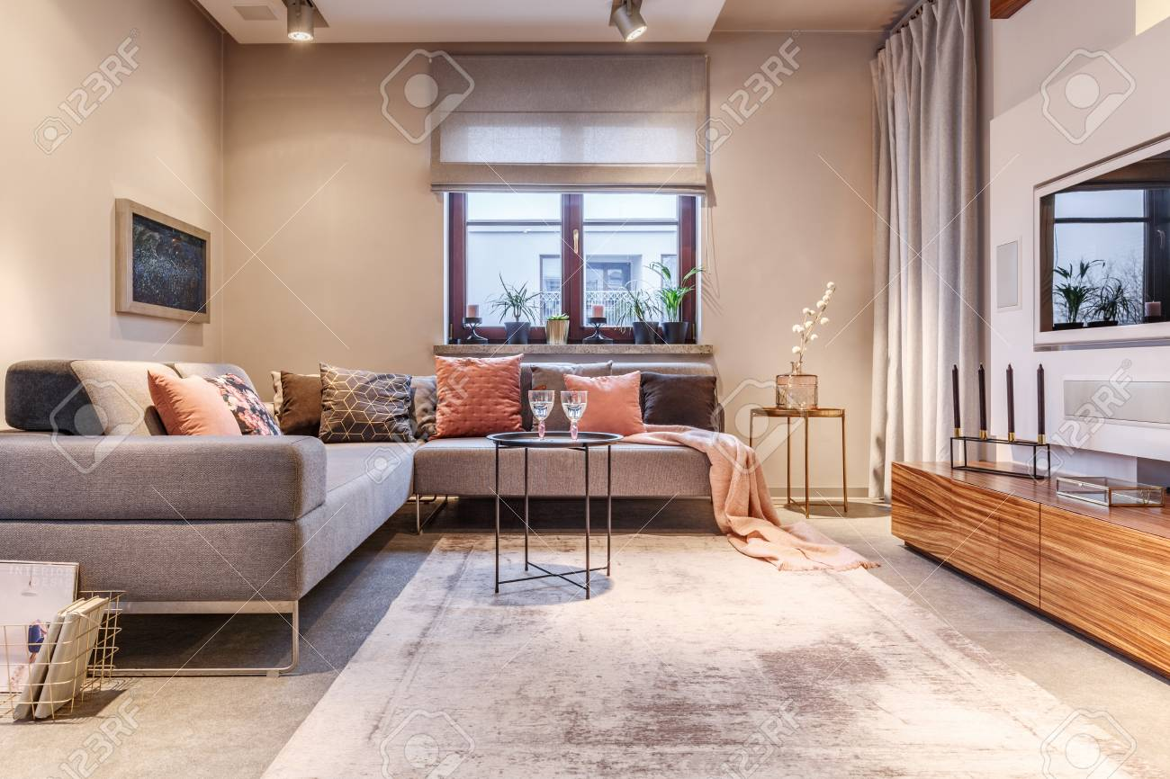 . Cozy living room interior with a big sofa  many cushions  wooden