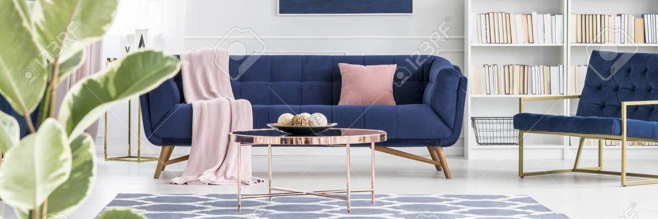 Pink pillow on navy blue sofa near armchair in elegant living..