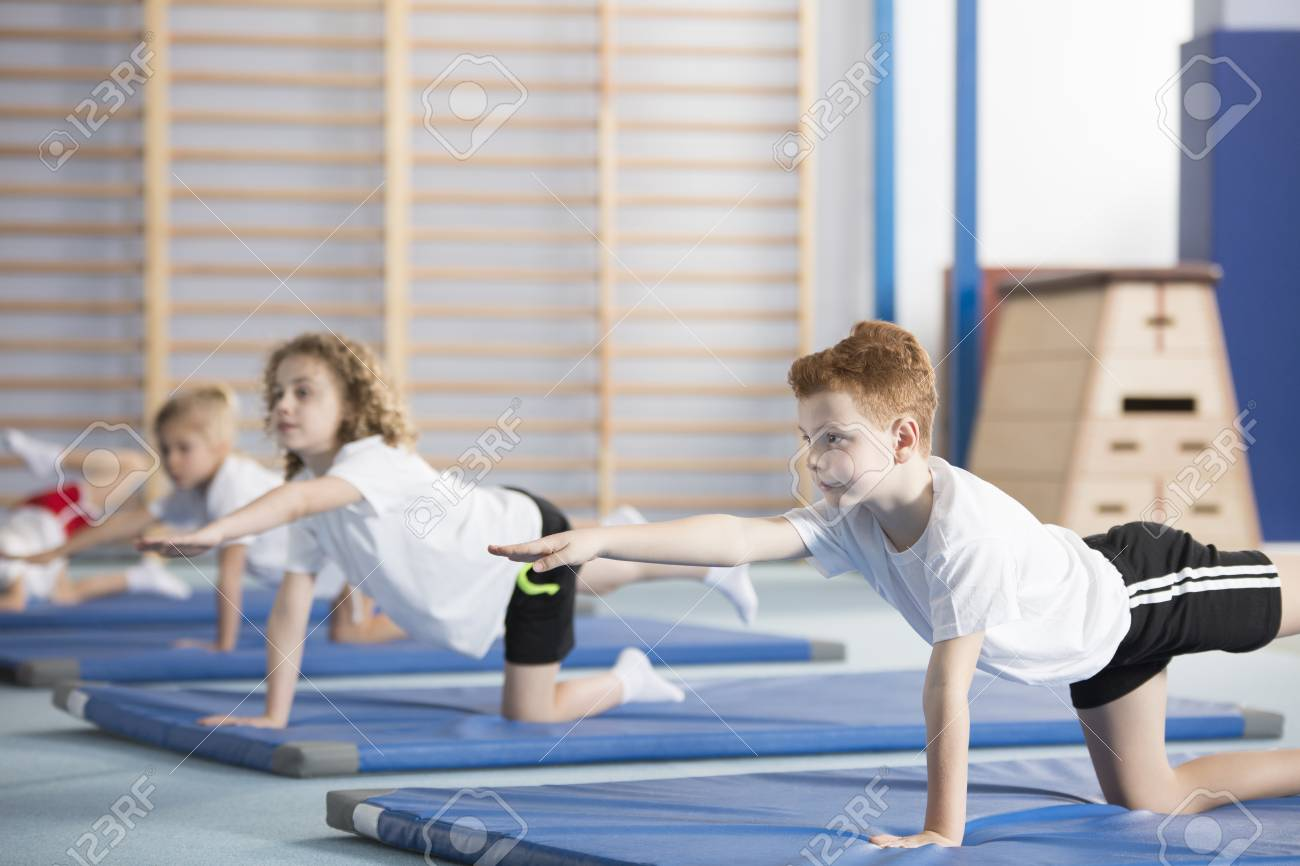 Group of children doing gymnastics on blue mats during physical education class at school - 101313363