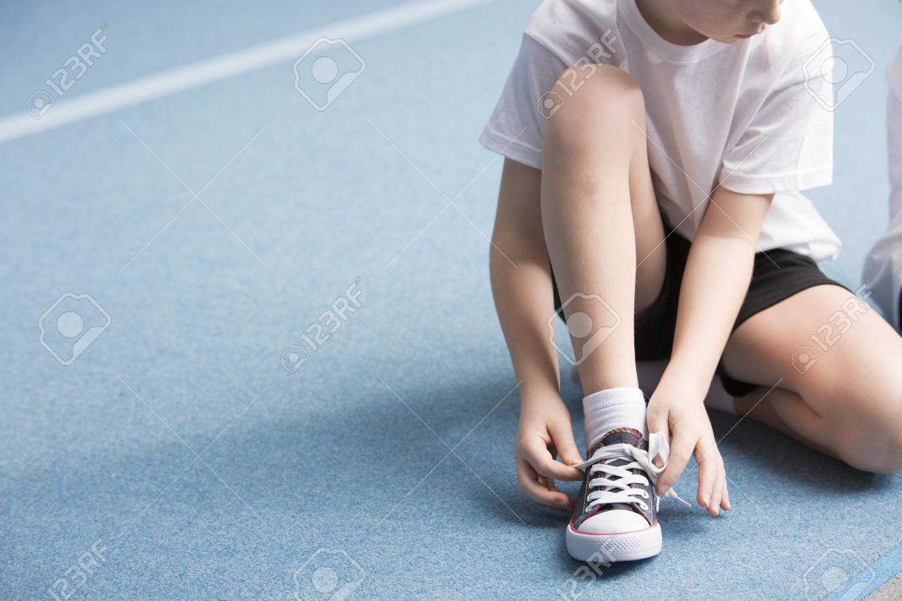 Cropped photo of a young boy tying his sports shoes on the court - 101313497